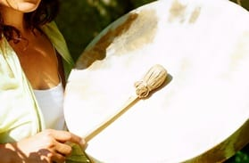 beautiful shamanic girl playing on shaman frame drum in the nature
