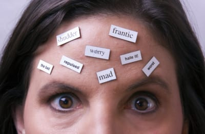 "Magnet words on female's forehead. Words are all negative. Implies ""negative thinking"" or thoughts."